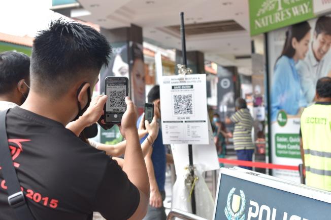 圖為在新加坡Mustafa Center外一名男子進入購物中心前掃描QR code,以利追蹤行動軌跡。美聯社