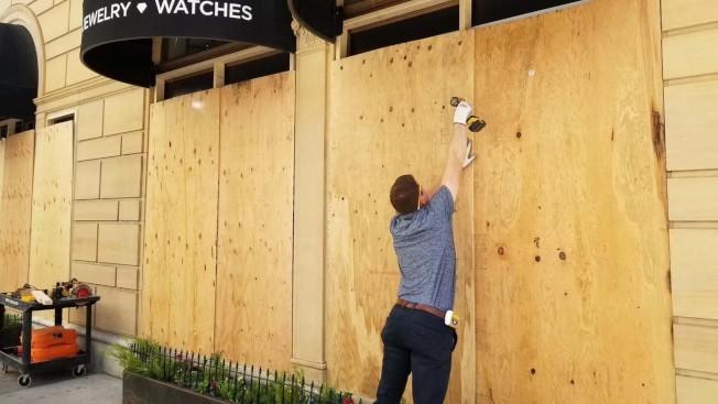 一名工人正在為遭破壞的店面釘上木板。(陳愛國提供)