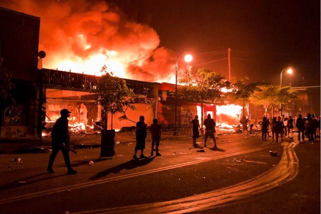 明尼蘇達州非裔佛洛伊德遭白人警察以膝壓頸致死,憤怒的群眾28日晚間在街上抗議,酒舖和商店被燒毀。 (Getty Images)