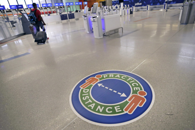最新研究顯示,在美國針對中國頒布旅行禁令前,新冠病毒已於1月中至2月初開始在美國傳播。圖為波士頓羅根機場要求旅客保持社交距離。(美聯社)