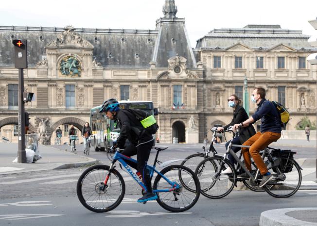 著名的羅浮宮博物館因應疫情,自3月中起關閉,將在7月6日重開。圖為一群自行車騎士經過羅浮宮博物館。(路透)