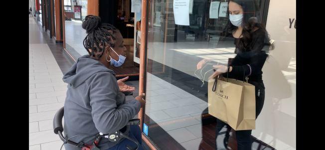 安大略購物中心Coach連鎖店,售貨員與非裔顧客隔著玻璃窗交易。(記者啟鉻/攝影)