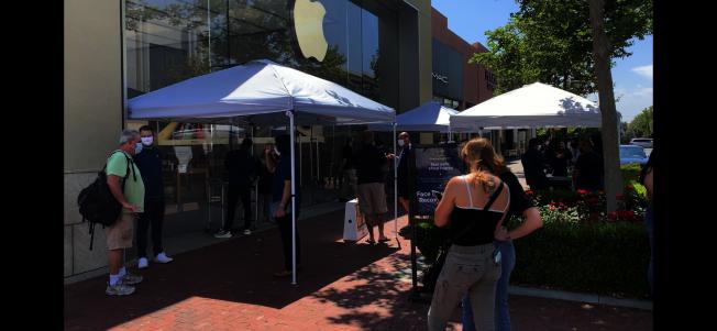 維多利亞花園步行街的蘋果手機店,顧客與職員在店外交易。(記者啟鉻/攝影)