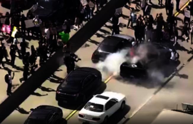 部分抗議者一度攻擊一些汽車,打碎汽車玻璃。(電視新聞截圖)
