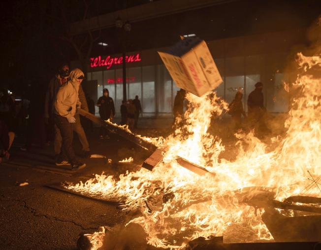 奧克蘭29日深夜街頭,一名示威者拉扯地上燃燒的紙板。(美聯社)