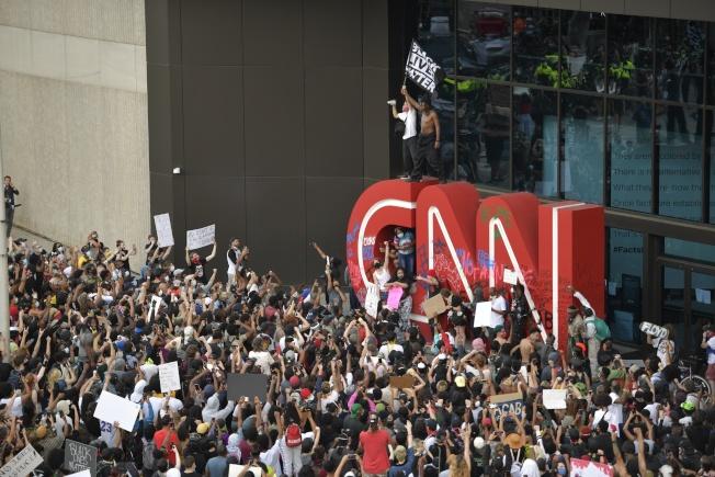 美國有線電視新聞網(CNN)位於亞特蘭大的總部29日遭示威者包圍,標誌遭噴漆塗鴉。(美聯社)