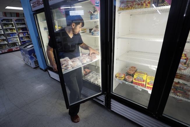 受到新冠疫情衝擊,美國食品價格4月大漲,讓民眾開銷暴增。圖為愛阿華州第摩因是一家超市的員工在上貨。(美聯社)