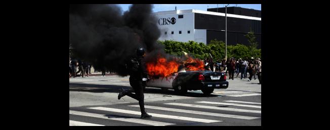 抗議者燒毀警車。(美聯社)
