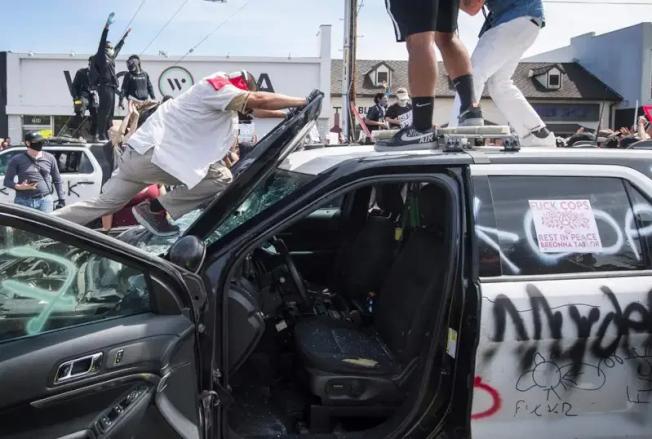 洛杉磯示威者砸警車。(法新社)