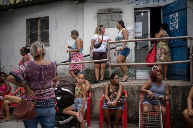 新冠肺炎對巴西貧民窟地區民眾造成嚴重威脅。圖為里約熱內盧的貧民窟人們等待非政府組織分發食物。(Getty Images)