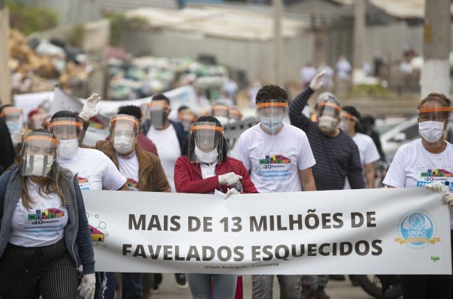 巴西聖保羅州最大貧民窟之一帕拉伊索波利斯居民5月18日高舉「貧民窟1300萬居民被遺忘」布條上街抗議,要求政府給予更多關注。(美聯社)