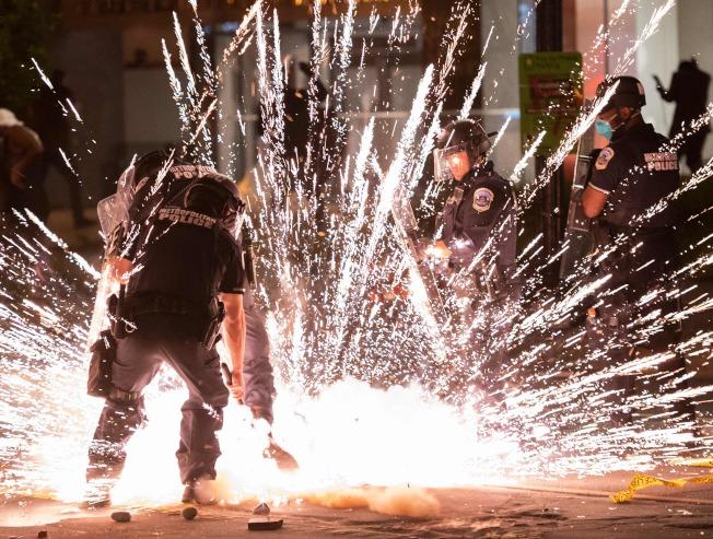 華府示威者5月30日朝警察扔鞭炮後,鞭炮在警察腳下爆炸。(Getty Images)