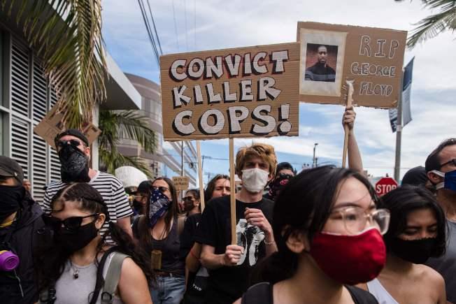 洛杉磯抗議示威遊行31日仍在持續,抗議標語是「定罪殺人警」。(美聯社)