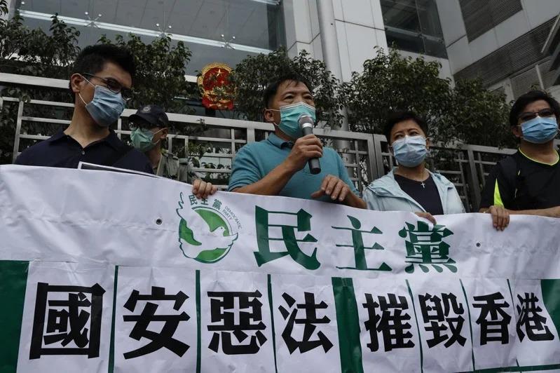 香港民主黨人士22日手拿寫有「國安惡法摧毀香港」的布條,到中聯辦前抗議。美聯社