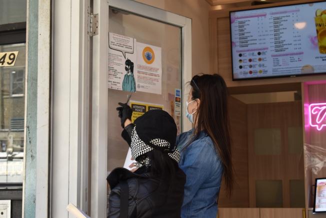志願者在店家張貼反歧視海報。(記者顏嘉瑩/攝影)