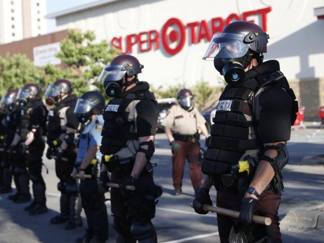 圖為明尼蘇達州的警察正在目標百貨前防護。(美聯社)