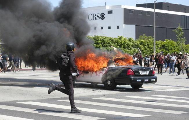 南加暴力示威頻頻,當局不得不以宵禁應對。圖為洛杉磯市有警車遭暴徒燒毀。(美聯社)