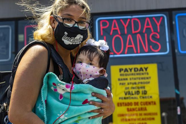 入夏以來,西南地區氣溫破百 ,已難全天戴口罩,防疫難度因此增加。圖為洛杉磯市一位母親抱著九個月大的孩子等巴士前往診所體檢。 (美聯社)