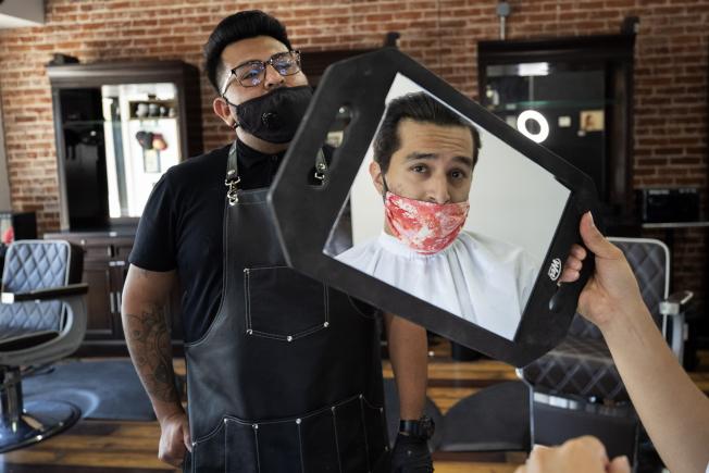 加州聖地牙哥放鬆社交距離管制 ,重開經濟,但科學家警告室內群聚可能造就「超級傳播者」。圖為聖地牙哥市一家髮廊重開,為顧客理髮。(美聯社)