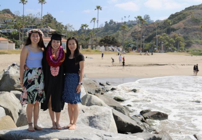 甘艾裕(中)大學畢業,家人祝賀海灘留影。(甘艾裕提供)