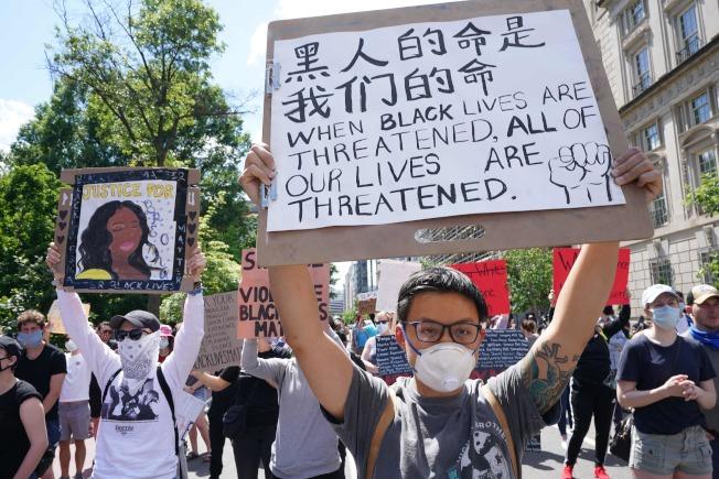 譴責警察暴力的華文標語31日出現在華盛頓的抗議遊行中。(美聯社)