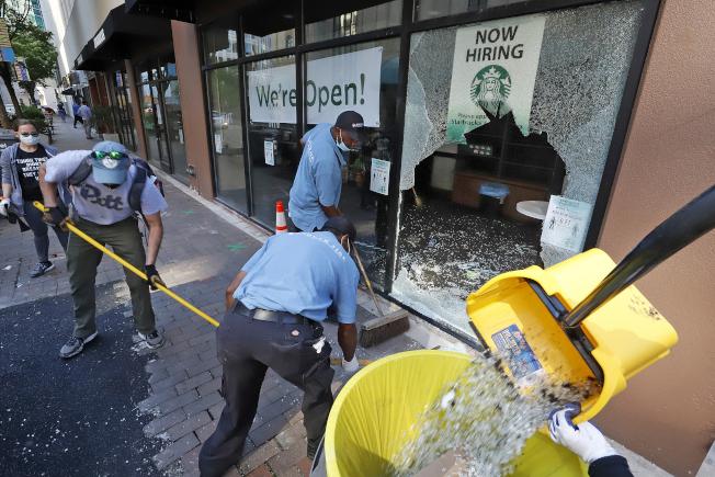 經過連續多天的抗爭暴亂,許多志願者31日出動清理遭到示威者暴力洗劫的商店。圖為洛杉磯的志願者在打掃被擊碎的店家玻璃。(美聯社)