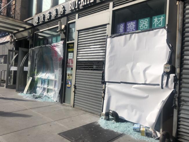 維康西藥房的兩扇大門被砸,可見玻璃滿地。(記者張晨/攝影)