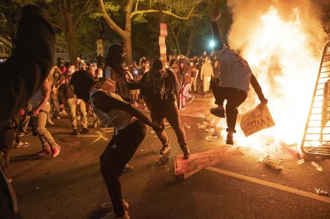 華府31日晚爆發示威,形勢一度升溫。示威者縱火路障,踩踏交通標識。(Getty Images)
