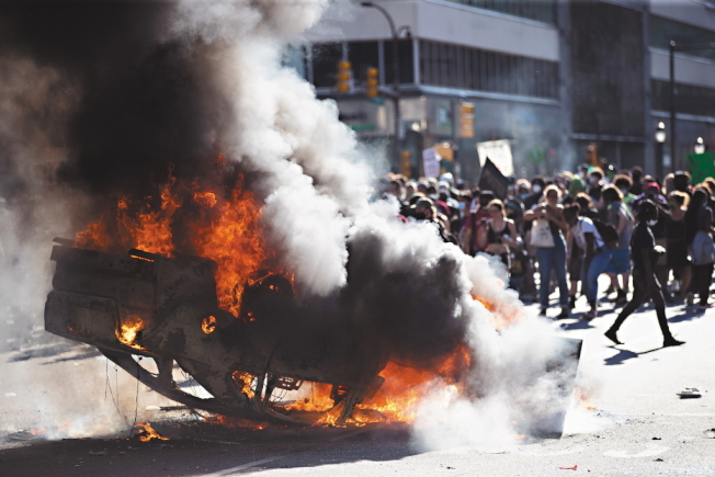 美國費城抗議者縱火焚燒一輛警車。(美聯社)
