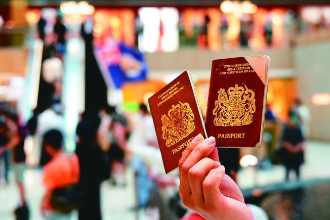反對港版國安法、要求國際支持的香港示威者,手中拿著英國國民海外護照。(路透)