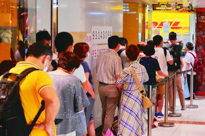 許多香港市民1日在DHL快遞公司外排隊,一大部分人是要寄文件到英國,申請或續領英國國民海外護照。(美聯社)