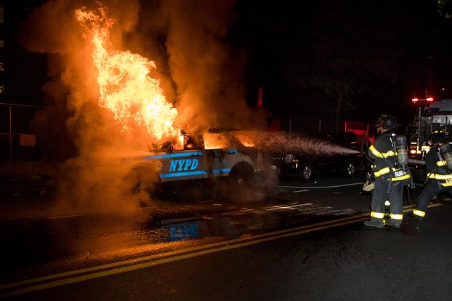 紐約持續多日的示威遊行中,眾多警車被示威者點燃、損毀。(新華社)