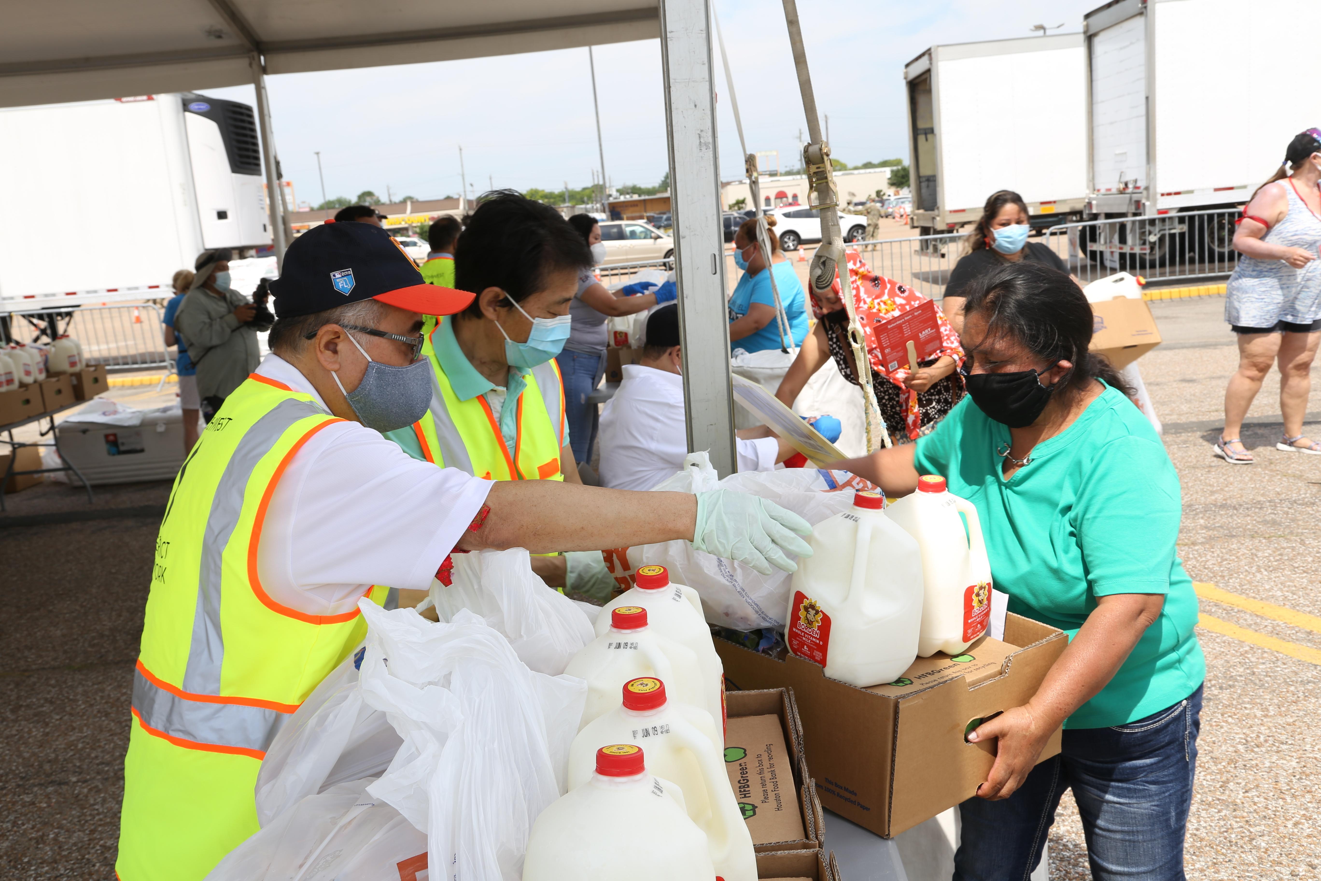 西南管理區區長李雄(左起)、理事David Peters協助派送食物給民眾。