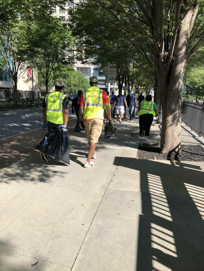 志工提著垃圾袋,沿街拾撿暴動留下的垃圾。(關學君提供)