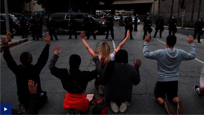 大量示威者在洛杉磯市政廳前下跪示威。前方有高度戒備的警員。(ABC7電視台)