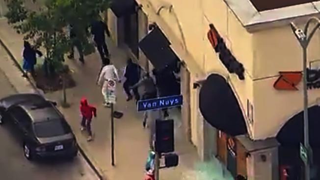 1日范奈斯(Van Nuys)地區的示威,有暴徒劫掠商店。圖為暴徒得手後逃離現場。(ABC7電視台)