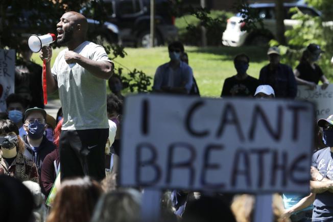 非裔佛洛伊德生前最後的一句哀求「我無法呼吸」,成為全美抗議種族歧視的精神標語。圖為在華盛頓州的示威者手持標語。(美聯社)