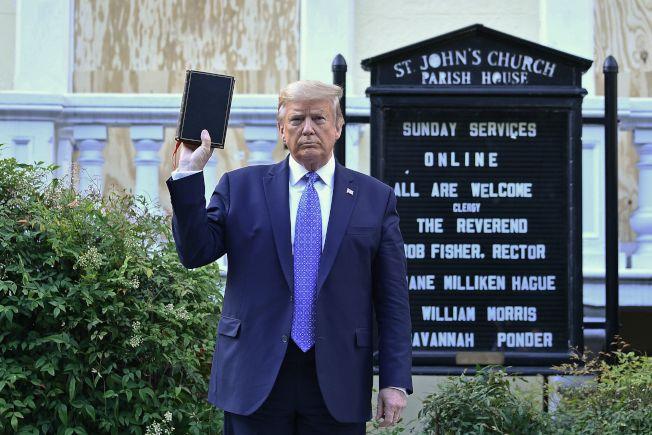 川普總統在白宮發表全國演講後探視日前遭示威者縱火焚燒的200年歷史古蹟聖約翰教會。圖為川普在教會外手持聖經。(Getty Images)