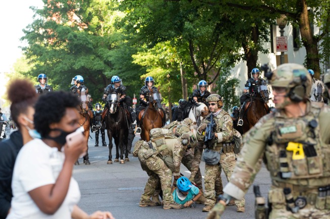 川普總統1日傍晚在白宮花園演講時,白宮外擠滿連日來不去的示威者。維安憲兵正在逮捕一名示威者。(Getty Images)