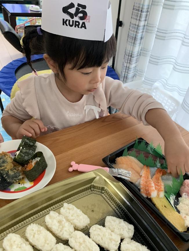 小朋友頭戴壽司店師傅的帽子認真地製作壽司。(取材自推特)