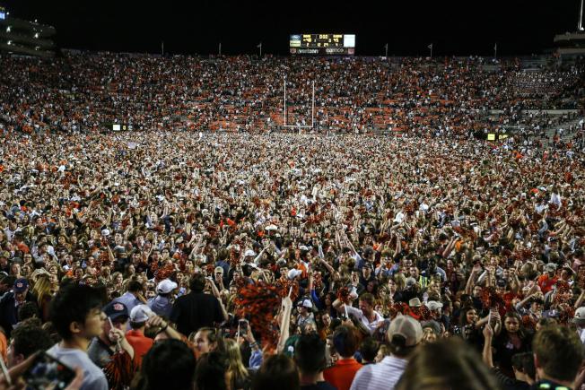 NCAA大學美足球迷衝入球場同慶的盛況。(美聯社)