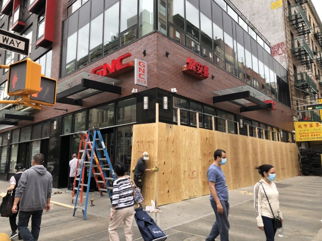 擔心遭暴徒破門,華埠商店釘上木板。(讀者提供)