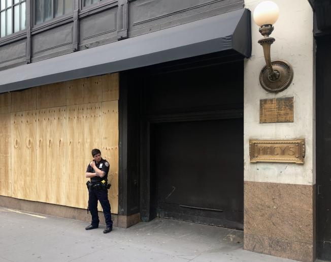 位於先鋒廣場的梅西百貨總店在宵禁第一夜遭暴徒洗劫,2日一早全店已用木板封死,周邊有市警執勤。(記者洪群超/攝影)