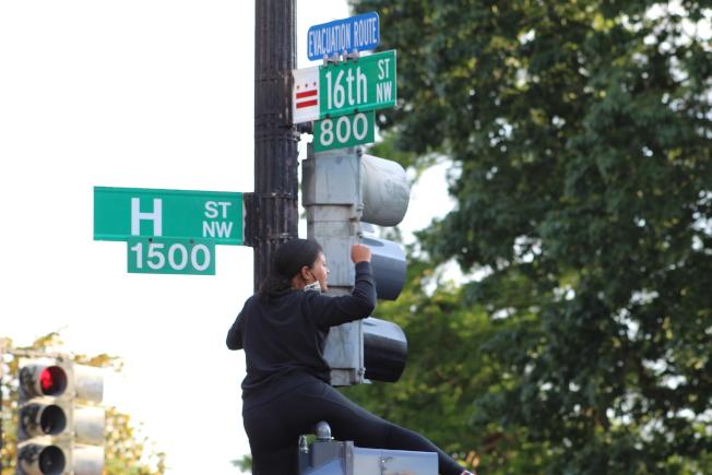抗議民眾爬到紅綠燈上,帶領群眾對著白宮喊口號。(記者張筠 / 攝影)