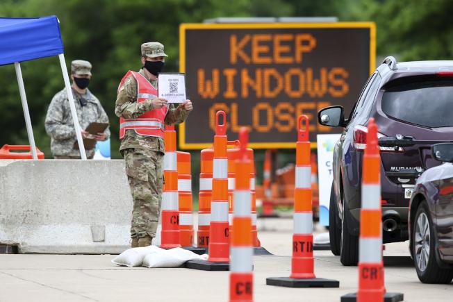 全美各地爆發的大規模抗議警察暴力的示威,導致許多新冠病毒檢測站關閉。圖為愛阿華州國民兵在一所社區大學外舉牌提醒駕車人參與檢測。(美聯社)