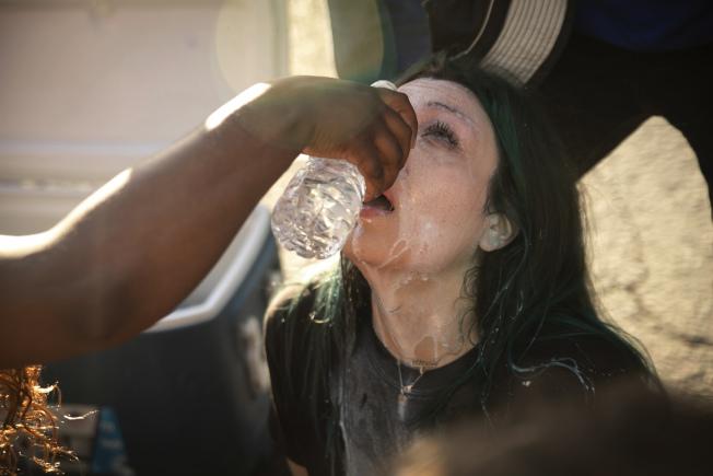 公衛專家指警方以催淚瓦斯、胡椒噴霧驅離群眾,恐導致病毒擴散。圖為華盛頓州一名示威者被催淚瓦斯擊中後正在清理。(美聯社)
