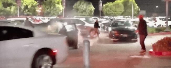 有人指揮劫匪將車一輛輛開走,現場還冒出車胎被縱火的濃煙。(社交媒體視頻截圖)