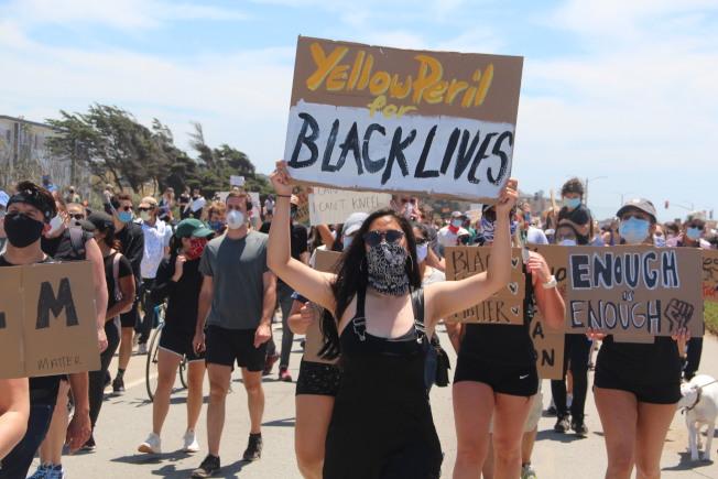 遊行隊伍的前端,有亞裔人士舉牌寫著「黃禍支持黑人的生命」(Yellow Peril for Black Lives)。(記者李晗 / 攝影)