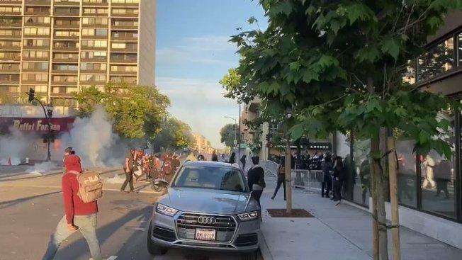 示威者向屋崙的警車投擲石塊,警方則發射催激瓦斯(左方)。(Getty Images)