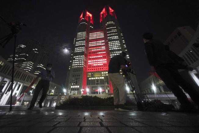 「東京警報」發布後,東京都政府大樓2日晚打上紅色燈光,提醒市民提高警覺防疫。(美聯社)